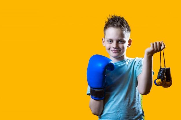 Surowy chłopiec w niebieskim rękawice bokserskie na jasnożółtym