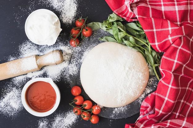 Surowy ciasto dla pizzy z składnikami na kuchennym kontuarze