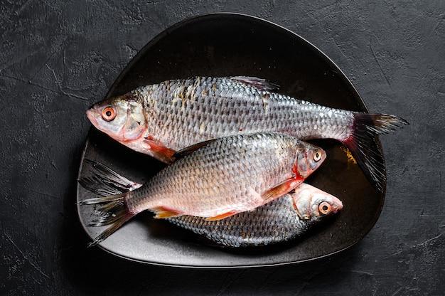 Surowy crucian karp na czarnym talerzu. ryby ekologiczne rzeczne. widok z góry