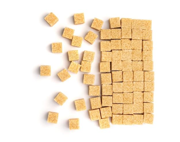 Surowy cukier brązowy na białym tle leżał płasko. nierafinowany cukier trzcinowy