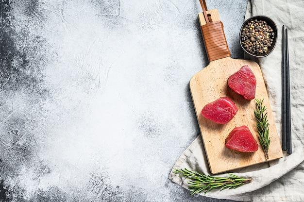 Surowy czerwony stek z tuńczyka. szare tło. widok z góry. miejsce na tekst