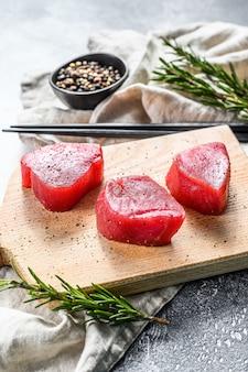 Surowy czerwony stek z tuńczyka. szare tło. widok z góry