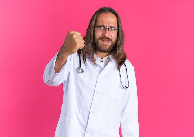 Surowy dorosły lekarz mężczyzna ubrany w szatę medyczną i stetoskop w okularach pokazujących pięść