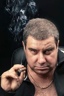 Surowy dorosły mężczyzna, patrzący pewnie w kamerę, palący cygaro. bandyta lub przestępca, szef grupy przestępczej. pionowy portret, zbliżenie twarzy, rosja.