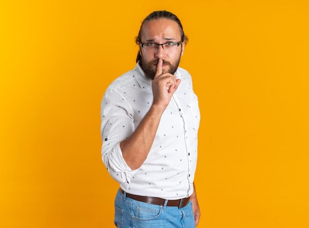 Surowy dorosły przystojny mężczyzna w okularach stojący w widoku profilu, wykonujący gest ciszy