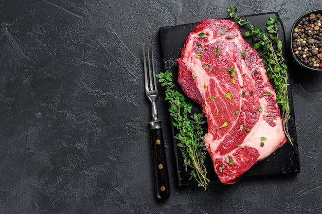 Surowy ekologiczny stek z mięsa chuck eye roll. czarne tło. widok z góry. skopiuj miejsce.
