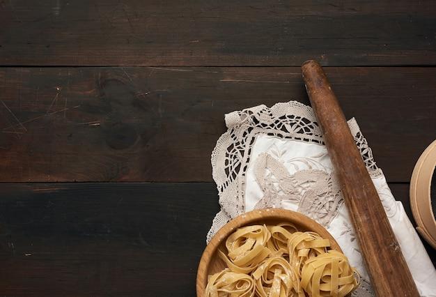 Surowy fettuccine makaron, drewniana toczna szpilka na brown drewnianej desce, odgórny widok