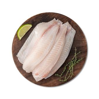 Surowy filet rybny tilapia z przyprawami na białym tle nad białym tłem.