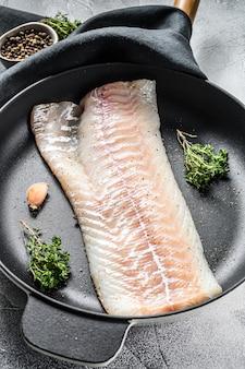 Surowy filet z dorsza z tymiankiem i ziołami na patelni. gotowanie świeżych ryb. szare tło. widok z góry