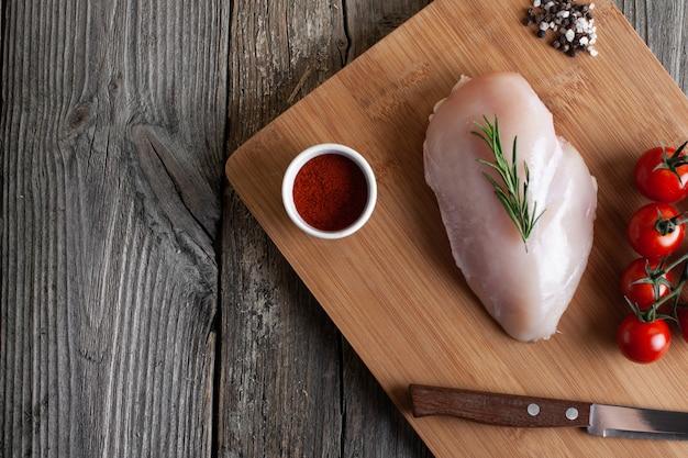 Surowy filet z kurczaka na desce do krojenia z przyprawami na drewnianym widok z góry na miejsce na płasko leżał
