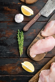 Surowy filet z kurczaka w panierce ze składnikiem, na ciemnym drewnianym stole, widok z góry