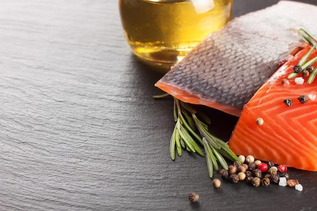 Surowy filet z łososia i przyprawy na ciemnym stole łupkowym