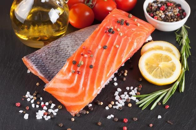 Surowy filet z łososia i składniki do gotowania na ciemnym tle łupków.