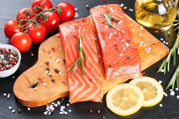 Surowy filet z łososia i składniki do gotowania na desce do krojenia i ciemnym tle łupków.