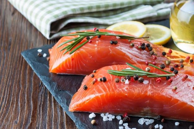 Surowy filet z łososia i składniki do gotowania na desce i brązowym drewnianym stole.