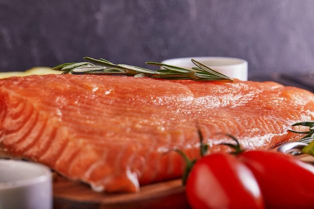 Surowy filet z łososia pieprz sól koperek cytrynowy rozmaryn i pomidory czereśniowe na ciemnym drewnianym stole.