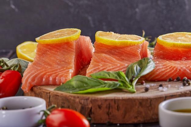 Surowy filet z łososia pokrojony na kawałki, sól pieprzowa koperek cytrynowy rozmaryn i pomidory koktajlowe na ciemnym drewnianym stole. widok z boku.