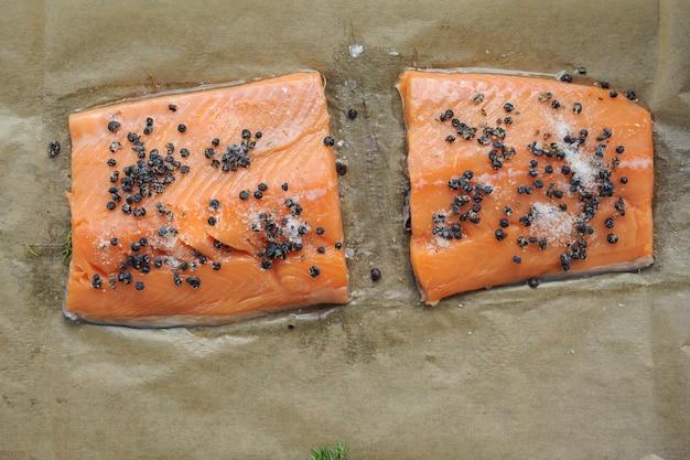 Surowy filet z łososia, solt i jagody jałowca do gotowania na brązowym papierze w stylu rustykalnym. widok z góry. horisontal.