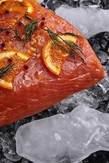 Surowy filet z łososia z plastrami pomarańczy na kawałkach lodu na czarnym tle