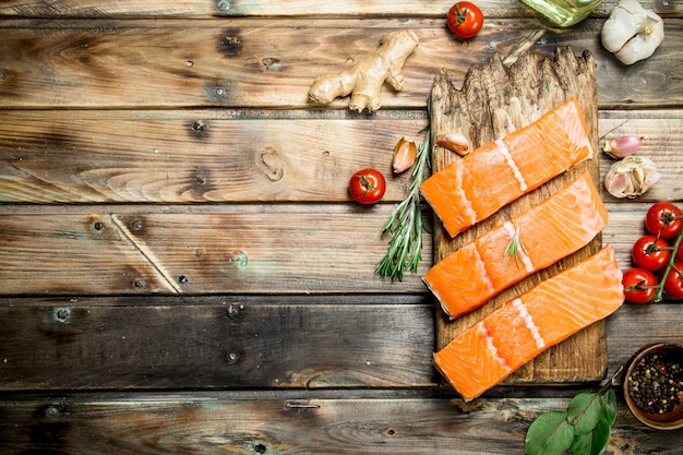 Surowy filet z łososia z pomidorami i przyprawami. na drewnianym tle.