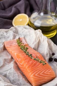 Surowy filet z łososia z rozmarynem, oliwą z oliwek i kawałkiem cytryny. zbliżenie