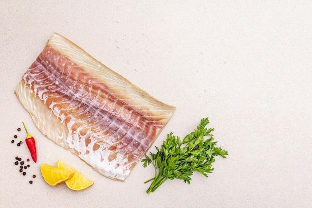 Surowy filet z mintaja (pollachius virens). świeże ryby dla zdrowego stylu życia. cytryna, pietruszka, sól morska, chili, czarny pieprz