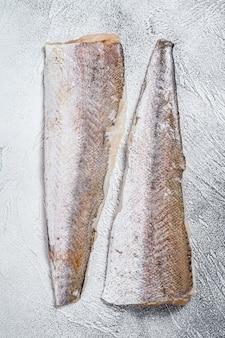 Surowy filet z morszczuka. białe tło. widok z góry.