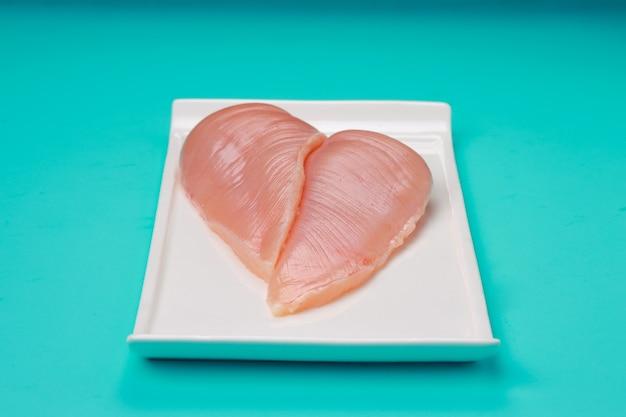 Surowy filet z piersi kurczaka bez skóry ułożony na płaskiej zastawie stołowej w kształcie białego prostokąta