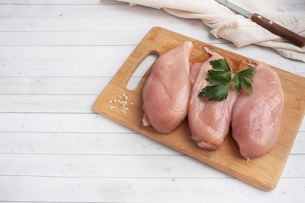 Surowy filet z piersi kurczaka, surowe mięso z kurczaka na desce do krojenia. biały, kopia przestrzeń.