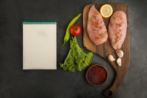 Surowy filet z piersi kurczaka z książeczką rachunków na boku