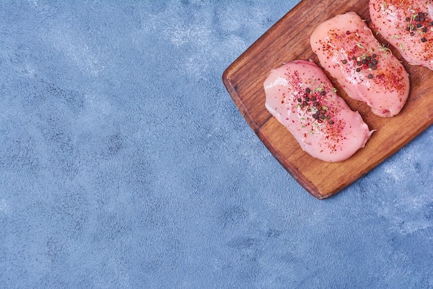 Surowy filet z przyprawami na desce na niebiesko