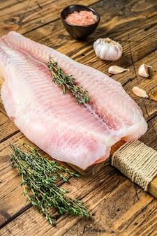 Surowy filet z ryby panga na desce do krojenia.
