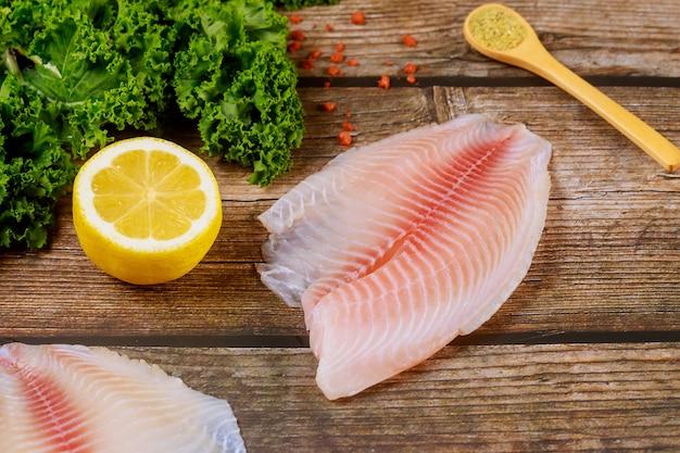 Surowy filet z ryby tilapia na stole z cytryną i przyprawami