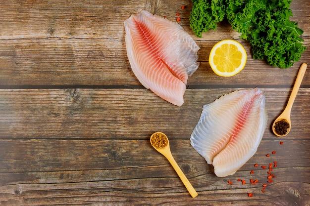 Surowy filet z ryby tilapia na stole z cytryną i przyprawami.