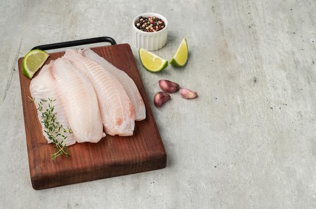 Surowy filet z ryby tilapia z przyprawami na desce.