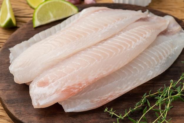 Surowy filet z ryby tilapia z przyprawami na drewnianym stole.