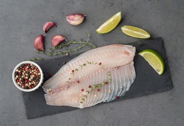 Surowy filet z ryby tilapia z przyprawami na tle kamienia.