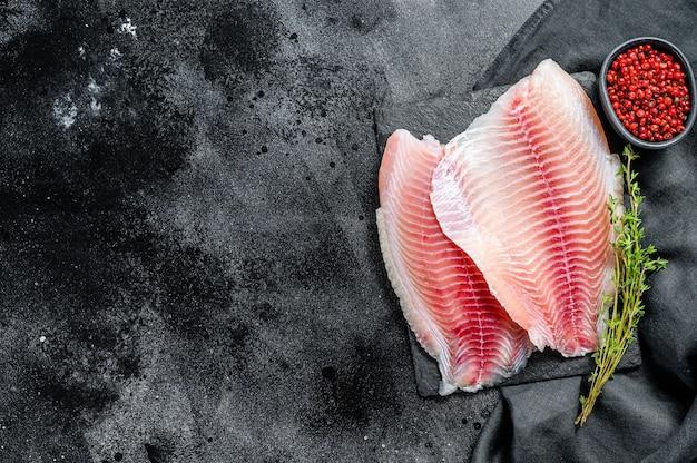Surowy filet z tilapii na desce do krojenia z tymiankiem i różowym pieprzem. czarne tło. widok z góry. skopiuj miejsce.