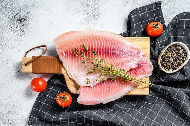 Surowy filet z tilapii na desce do krojenia