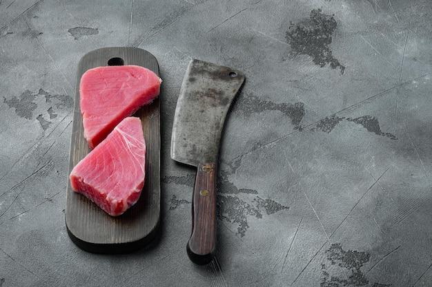 Surowy filet z tuńczyka ekologicznego. zestaw owoców morza, na drewnianej desce do krojenia i stary nóż rzeźniczy, na szarym tle kamienia, z copyspace i miejscem na tekst