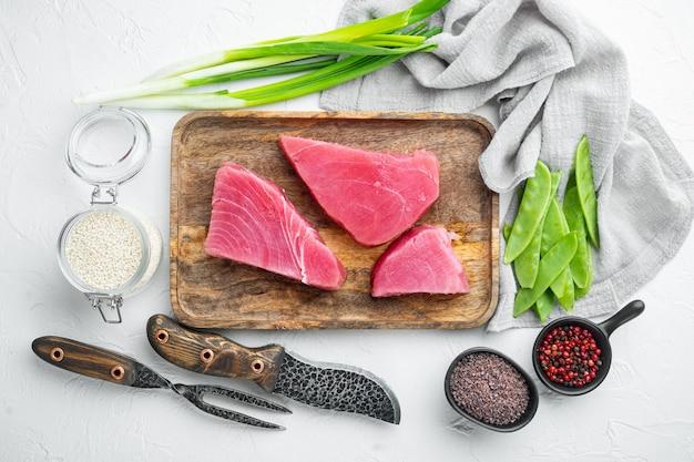 Surowy filet z tuńczyka. owoce morza z cukrowym zielonym groszkiem, sezamem i zestawem składników, na drewnianej tacy, na białym kamieniu