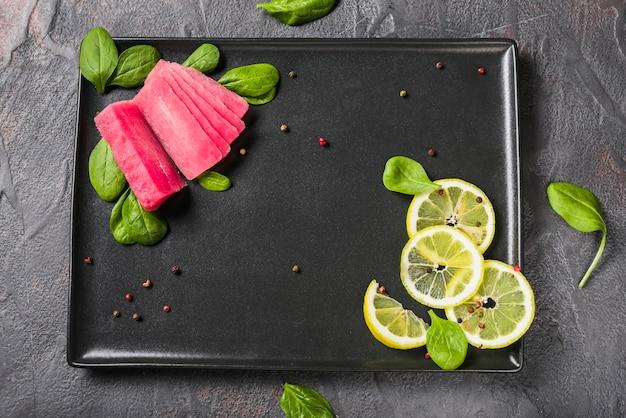 Surowy filet z tuńczyka z liśćmi bazylii i cytryną