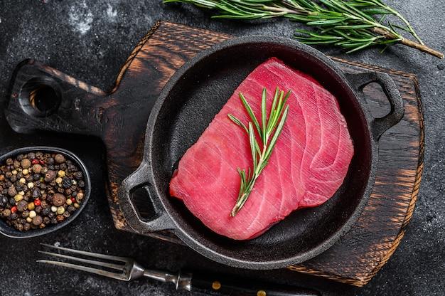 Surowy filet z tuńczyka z rozmarynem na patelni. czarne tło. widok z góry.