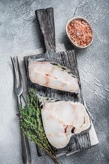 Surowy filet z wilczaka stek na drewnianą deską do krojenia. białe tło. widok z góry.
