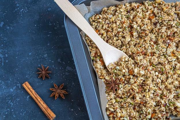 Surowy granol z łyżką na blasze do pieczenia na ciemnoniebieskim tle
