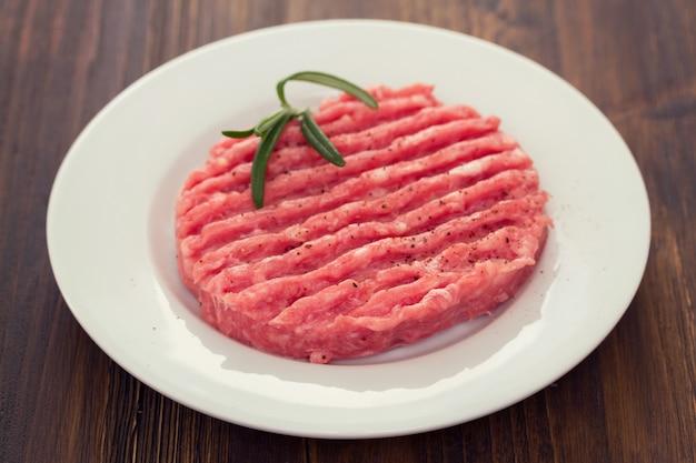 Surowy hamburger na bielu talerzu na drewnianej powierzchni