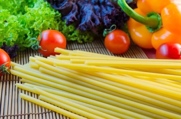 Surowy i długi makaron oraz warzywa na stole