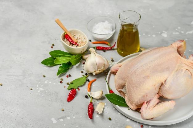Surowy indyk z przyprawami liść laurowy, czosnek, sól, papryka chili i oliwa z oliwek. przepis na rodzinny obiad. dieta ketonowa.