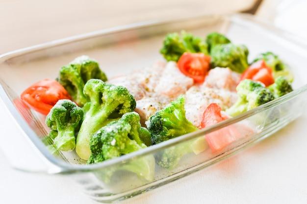 Surowy indyk z warzywami na blasze do pieczenia. kalafior spomidora. danie z surową przyprawą z indyka na szklanej patelni do pieczenia, widok z góry