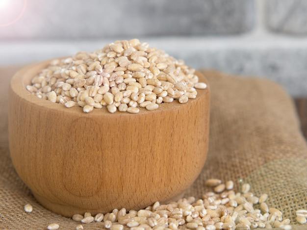 Surowy jęczmień perłowy w drewnianym talerzu, a obok niego drewniana łyżka, rozlewający się na ciemny drewniany stół